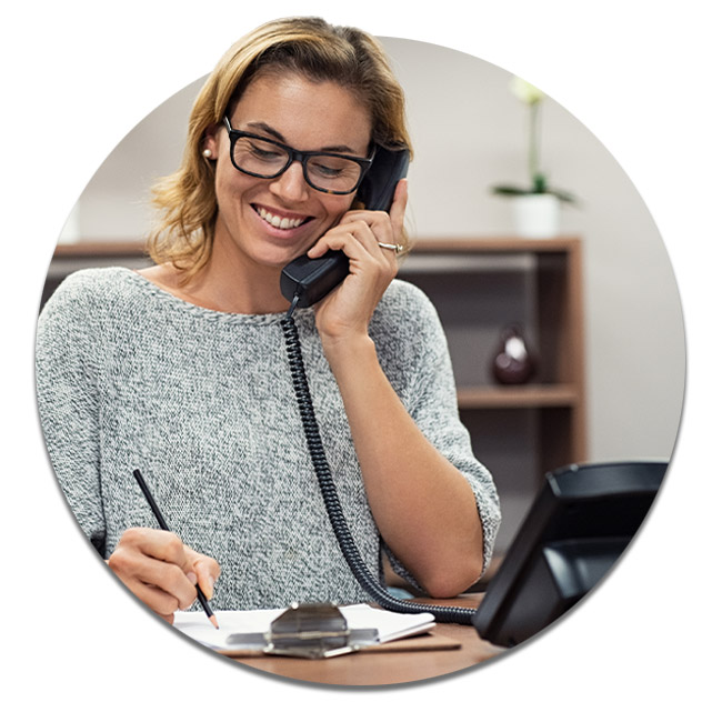 Casual smiling business woman sitting at desk making telephone call and taking note.