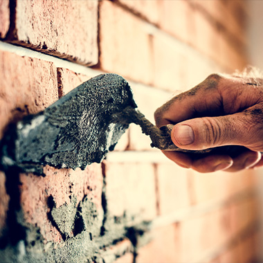 A man cementing bricks due to structural damage